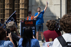 London, UK. 20th July, 2021. Matthew Tovey, a NHS Wales nurse from Merthyr Tydfil, addresses fellow NHS workers from the grassroots NHSPay15 campaign outside Parliament before a march to 10 Downing Street to present his petition signed by over 800,000 people calling for a 15% pay rise for NHS workers. At the time of presentation of the petition, the government was believed to be preparing to offer NHS workers a 3% pay rise in 'recognition of the unique impact of the pandemic on the NHS'.