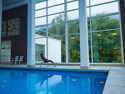 Woman relaxing by swimming pool of Paracelsus-Therme, Bad Liebenzell, Baden-Württemberg, Germany