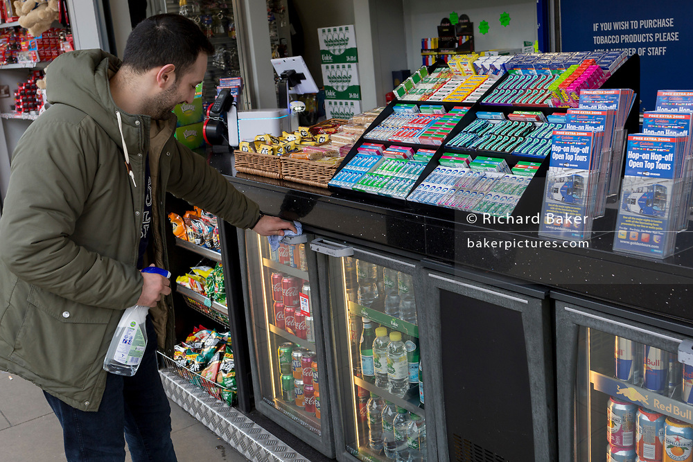 As the UK government urged that all Britons should avoid non-essential travel abroad in order to combat the Coronavirus pandemic in Britain and small businesses suffer from lack of trade, a snack and drinks vendor wipes down handles and surfaces every 15mins outside Kings Cross railway station, on 17th March 2020, in London, England.