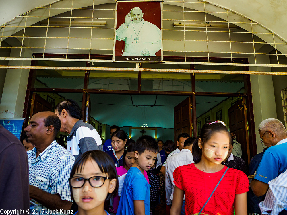 19 NOVEMBER 2017 - HWAMBI, YANGON REGION, MYANMAR: People walk under a portrait of Pope Francis as they leave Sacred Heart's Catholic Church in Hwambi, about 90 minutes north of Yangon, after mass. Catholics in Myanmar are preparing for the visit of Pope Francis. He is coming to the Buddhist majority country November 27-30. There about 500,000 Catholics in Myanmar, about 1% of the population. Catholicism was originally brought to what is now Myanmar more than 500 years ago by Portuguese missionaries and traders.    PHOTO BY JACK KURTZ