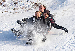 © Licensed to London News Pictures 11/02/2021.        Sevenoaks, UK. Three friends on one sledge. Lockdown sledging fun at Knole Park in Sevenoaks, Kent as the freezing cold weather continues in Kent and the South East with more snow expected. Photo credit:Grant Falvey/LNP