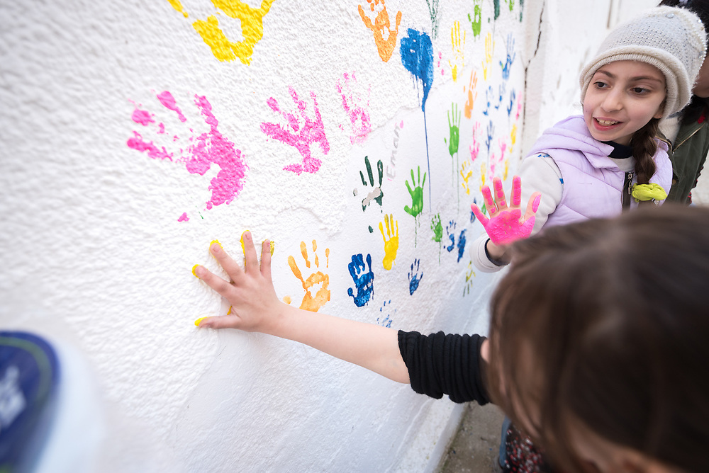 17 February 2020, Zarqa, Jordan: Two girls paint their handmarks on the wall of the Lutheran World Federation community centre in Zarqa. Through a variety of activities, the Lutheran World Federation community centre in Zarqa serves to offer psychosocial support and strengthen social cohesion between Syrian, Iraqi and other refugees in Jordan and their host communities.