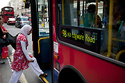 Muslim woman climbs aboard a bus in central London.