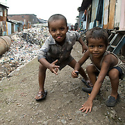 Boys play on the giant water pipe that carries drinking water to Mumbai. The recycling area in Dharavi is built on top of the giant pipes but very few homes here have running water.