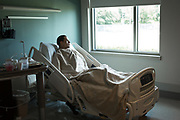 Angel Santiago, a Pulse survivor shot in both legs, stares out the window of his room at HealthSouth Rehabilitation Hospital in Altamonte Springs, Florida, U.S.
