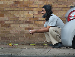 © Licensed to London News Pictures. 13/11/2015. London, UK.  Former Guantanamo detainee Shaker Aamer squats outside his home as he tries to entice a cat with some food. Shaker Aamer was freed recently after being incarcerated in the US prison located in Cuba since 2002.  Photo credit: Peter Macdiarmid/LNP