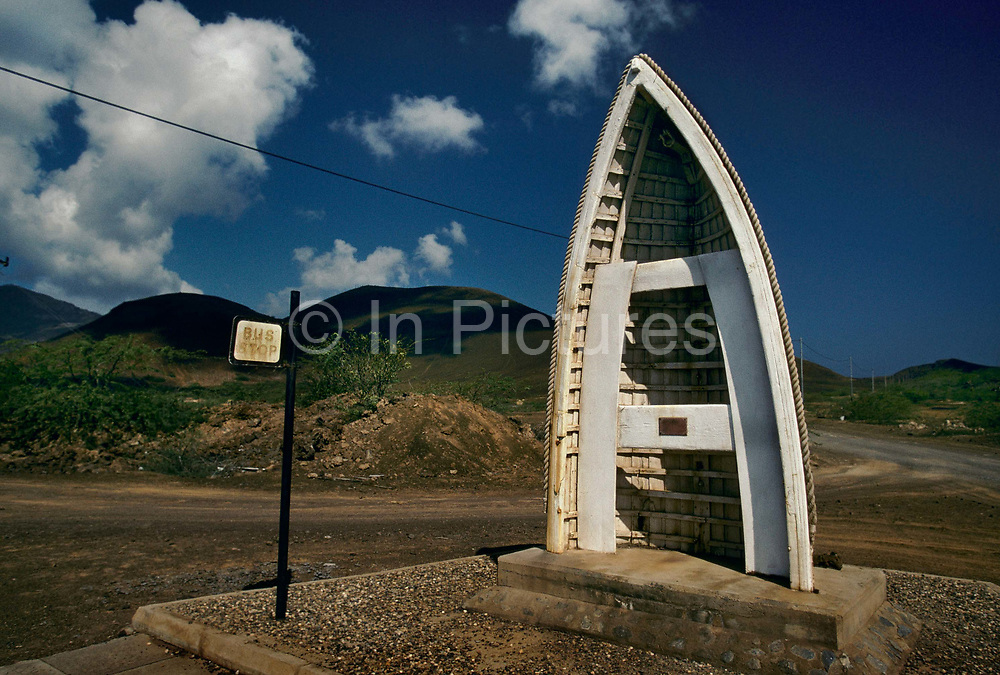 Bus shelter made from a boat, 27th May 1997, on Ascension, a small area of approximately 88 km² isolated volcanic island in the equatorial waters of the South Atlantic Ocean, roughly midway between the horn of South America and Africa. It is governed as part of the British Overseas Territory of Saint Helena, Ascension and Tristan da Cunha. Organised settlement of Ascension Island began in 1815, when the British garrisoned it as a precaution after imprisoning Napoleon I on Saint Helena. In January 2016 the UK Government announced that an area around Ascension Island was to become a huge marine reserve, to protect its varied and unique ecosystem, including some of the largest marlin in the world, large populations of green turtle, and the islands own species of frigate bird. With an area of 234,291 square kilometres 90,460 sq mi, slightly more than half of the reserve will be closed to fishing.