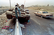 Cars drive past a destroyed Iraqi Army T-72 tank left behind by retreating soldiers following the liberation of Kuwait March 1, 1991 in Kuwait City, Kuwait. After four days of fighting, all Iraqi troops were expelled from Kuwait, ending a nearly seven-month occupation of Kuwait by Iraq.