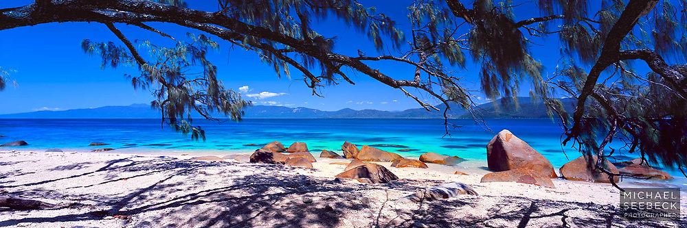 Branches of casuarina trees sway gently over beautiful Nudey Beach on Fitzroy Island, the aqua waters lapping up onto the coral beach amongst smooth angular boulders.<br /> <br /> Code: HAQI0002<br /> <br /> Limited Edition Print