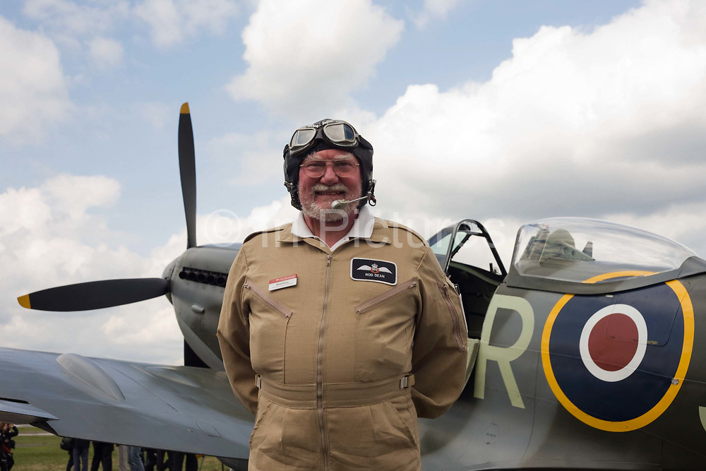Farnborough International Airshow Flight Operations Director Rod Dean poses in front of AVM Cliff Spink's Spitfire that he has just flown a display in at the Farnborough Air Show media launch. Posing with hands behind his back and with his flying helmet complete with goggles on his forehead, the veteran Hunter fighter pilot is now retired from the RAF but as a young Pilot Officer, won the first-ever International Air Tattoo flying trophy in 1972. The Spitfire's canopy is left open and its propeller has stopped turning as the aircraft awaits refuelling. Dean's role at the Farnborough show is of organiser of the flying programme and the static ground display.