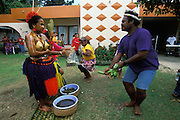 Members of her husbands family dance for a young mother and present her with gifts when she emerges and shows hereself at the end of her first childbirth ritual. Palau, Micronesia, in February, 2005. For five days prior to this coming-out ceremony, the young mother has twice daily been given hot cleansing baths by a medicine woman. Every Palauan woman goes through a first childbirth ritual, a ngasech, two to three months after giving birth for the first time. The grass skirt which this woman is wearing is made of wool.