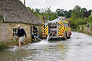 Firemen pump water out of flooded home in Naunton, The Cotswolds, Gloucestershire, England, United Kingdom