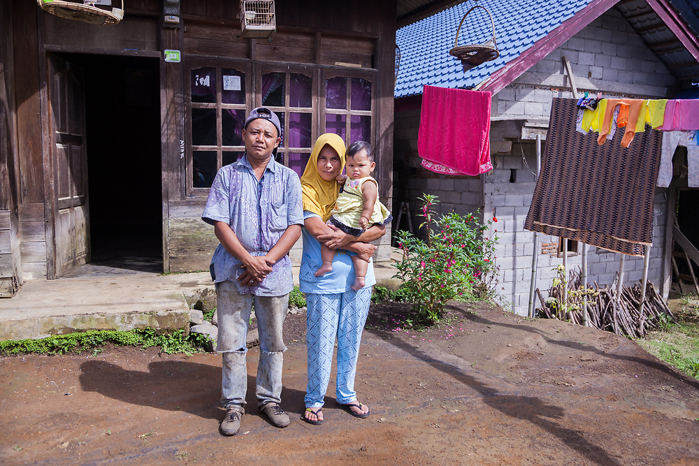 Pak Rino (44), wife Bariah (43), and youngest daughter Kaliah (9 months), pose for a portrait in front of their home in Wanosari Village. Pak Rino has been a member of Permato Gayo since 2009 and since then his earnings have increased and he is able to support his family.
