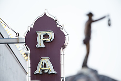 The Nightwatchman sculpture on top of City Hall, honoring men who protected town in early 1900s, and portion of Palace Theater sign, Grapevine, Texas USA
