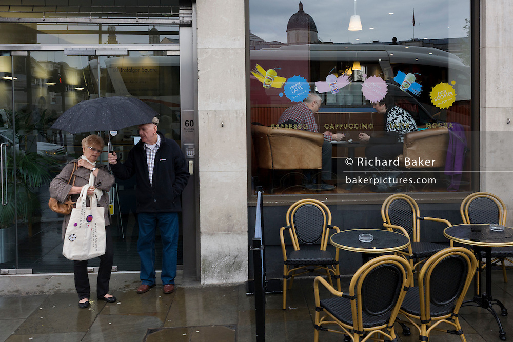 Tourist couple rest during a tour of London in the rain alongside others enjoying a drier morning in a cafe.