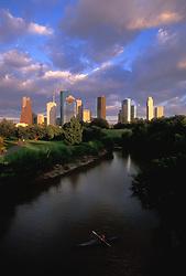 Kayaker on Buffalo Bayou with Houston, Texas skyline and beautiful sky.