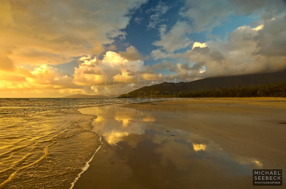 Wet sand reflections of overhead clouds on Myall Beach, near Cape Tribulation.