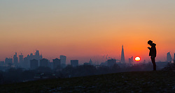 London, December 12 2017. A young man looks at his phone as the sun rises on a clear very cold morning in London, seen from Primrose Hill in Camden. © Paul Davey