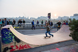 London, UK. 17th April 2019. A boy enjoys skateboarding at sunset on Waterloo bridge during the third day of International Rebellion activities by climate change activists from Extinction Rebellion.