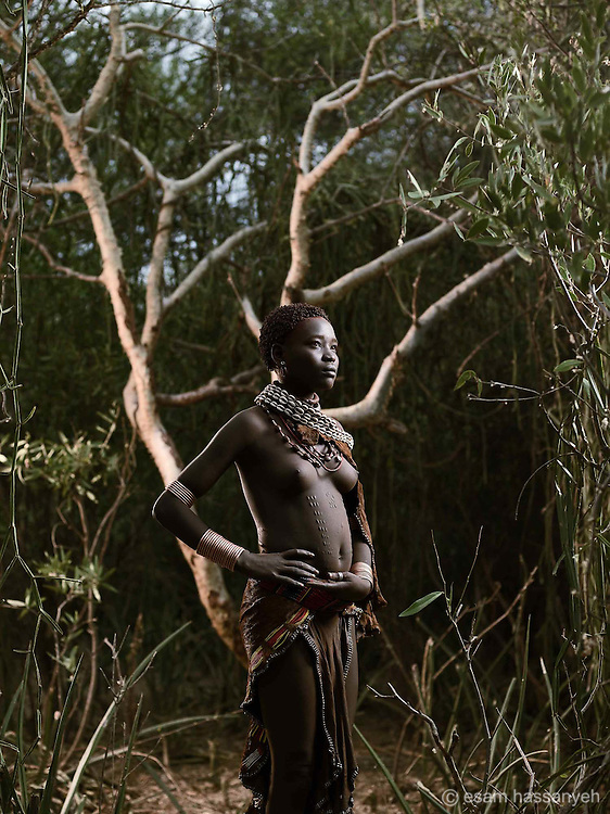 Portrait of Gai Dibo, Lower Omo Valley, Ethiopia.<br /> <br /> Gai Dibo is the first wife of a Hamer.<br /> <br /> The patterned seen on her stomach is decorative. The skin is pinched and a swift nick is made with a sharp knife. The entire pattern is cut at the same time so that the when the body heals, the scarring is even.