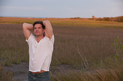 Man outdoors by a marsh catching a breeze