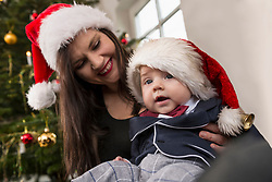 Mother with baby boy wearing santa hat