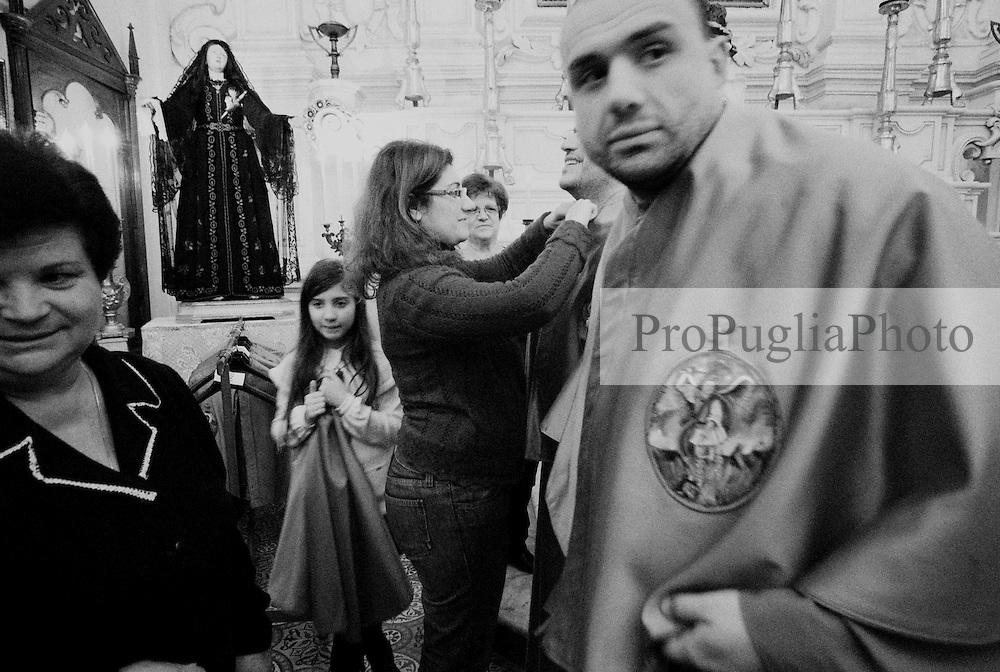 Reportage sulla processione del venerdi santo a Gallipoli...donne vestono i confratelli sull'altare della chiesa
