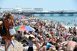 © Licensed to London News Pictures. 25/06/2020. Brighton, UK. Members of the public relax in the hot weather on a busy Brighton seafront in East Sussex, during a heatwave that is expected to bring record temperatures.  Photo credit: Liz Pearce/LNP
