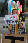 A man holds a sign saying Cancel the Olympics as people take part in a demonstration against the delayed 2020 Tokyo Olympics Games in Gaiemmae, Tokyo, Japan. Sunday May 9th 2021. About 100 people took part in a demo outside the Japanese Olympic Committee museum and marched around the new Olympic Stadium to protest holding the event while the  the COVID-19 pandemic is still seriously affecting Japan.