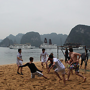 Locals and tourists play football on Titop Island, Ha Long Bay, Vietnam. The bay consists of a dense cluster of 1,969 limestone monolithic islands. Ha Long Bay, is a UNESCO World Heritage Site, and a popular tourist destination. Ha Long, Bay, Vietnam. 11th March 2012. Photo Tim Clayton