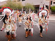 "03 DECEMBER 2011 - PHOENIX, AZ:   Matachine dance troupes perform during a procession to honor the Virgin of Guadalupe in Phoenix Saturday. The Phoenix diocese of the Roman Catholic Church held its Sixth Annual Honor Your Mother Day Saturday to honor the Virgin of Guadalupe. According to Mexican Catholic tradition, on December 9, 1531 Juan Diego, an indigenous peasant, had a vision of a young woman while he was on a hill in the Tepeyac desert, near Mexico City. The woman told him to build a church exactly on the spot where they were standing. He told the local bishop, who asked for some proof. He went back and had the vision again. He told the lady that the bishop wanted proof, and she said ""Bring the roses behind you."" Turning to look, he found a rose bush growing behind him. He cut the roses, placed them in his poncho and returned to the bishop, saying he had brought proof. When he opened his poncho, instead of roses, there was an image of the young lady in the vision. The Virgin is now honored on Dec 12 in Catholic churches throughout Latin America and in Hispanic communitied in the US.    PHOTO BY JACK KURTZ"