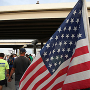 An American flag is seen during a protest parade prior to the Republican National Convention in Tampa, Fla. on Wednesday, August 29, 2012. (AP Photo/Alex Menendez)