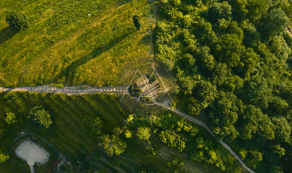 Aerial view of the top of a stepped hill illuminated by late afternoon light in the Po Valley, Italy.