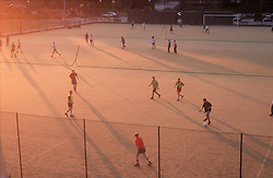 Footballers playing game of football on playing field,