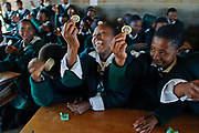 Tenth grade students from left: Majobo Mapesnoane 16, Limakatso Romajake 16, and Ronsang Rakobuoa 16; giggle as they hold a condom in their classroom. Contrary to common fears or stereotypes, extensive research has detected little evidence that sex education leads to an increase in sexual activity.