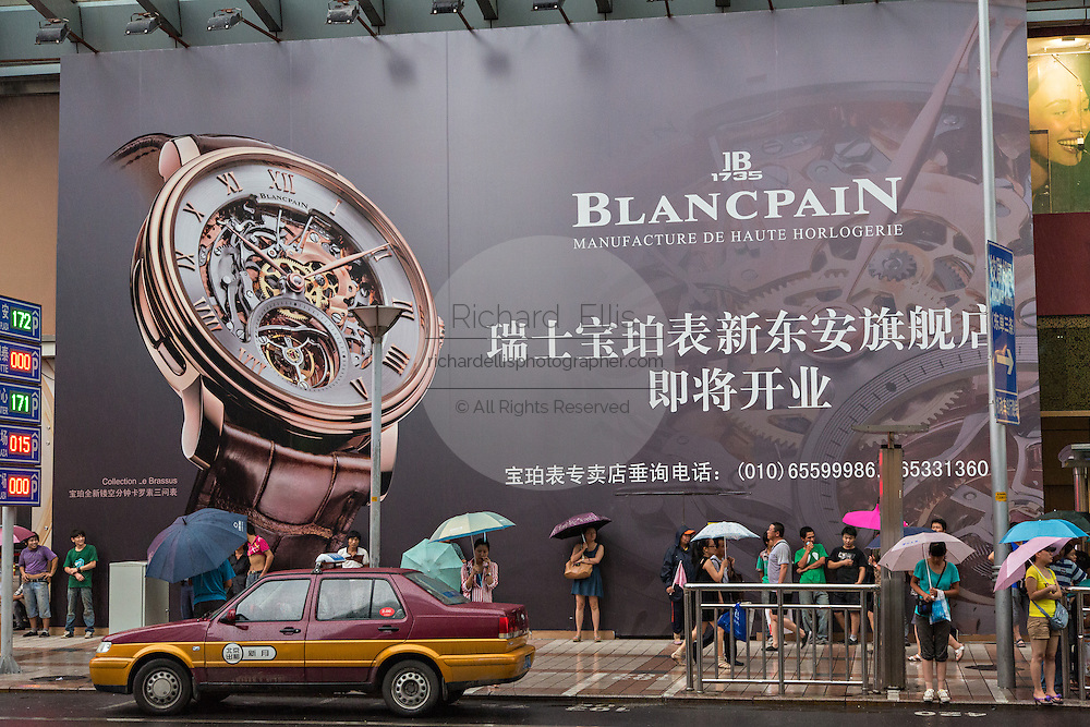 Giant advertisement for luxury watches along Wangfujing Street shopping district on a rainy day in Beijing, China