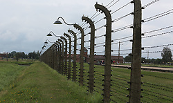 Barbed wire fences at the Auschwitz-Birkenau Nazi concentration camps in Auschwitz, Poland on September 3, 2017. Auschwitz concentration camp was a network of German Nazi concentration camps and extermination camps built and operated by the Third Reich in Polish areas annexed by Nazi Germany during WWII. It consisted of Auschwitz I (the original camp), Auschwitz II–Birkenau (a combination concentration/extermination camp), Auschwitz II–Monowitz (a labor camp to staff an IG Farben factory), and 45 satellite camps. In September 1941, Auschwitz II–Birkenau went on to become a major site of the Nazi Final Solution to the Jewish Question. From early 1942 until late 1944, transport trains delivered Jews to the camp's gas chambers from all over German-occupied Europe, where they were killed en masse with the pesticide Zyklon B. An estimated 1.3 million people were sent to the camp, of whom at least 1.1million died. Around 90 percent of those killed were Jewish; approximately 1 in 6 Jews killed in the Holocaust died at the camp. Others deported to Auschwitz included 150,000 Poles, 23,000 Romani and Sinti, 15,000 Soviet prisoners of war, 400 Jehovah's Witnesses, and tens of thousands of others of diverse nationalities, including an unknown number of homosexuals. Many of those not killed in the gas chambers died of starvation, forced labor, infectious diseases, individual executions, and medical experiments. In 1947, Poland founded a museum on the site of Auschwitz I and II, and in 1979, it was named a UNESCO World Heritage Site. Photo by Somer/ABACAPRESS.COM