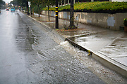 Heavy rains flow down streets into Street Gutters and Storm Drains and eventually Ballona Creek, a nine-mile waterway that drains the Los Angeles basin. Urban runoff carries an assortment of trash and debris from catch basins where a network of pipes and open channels create a pathway to the Ocean at Santa Monica Bay. Culver City, Los Angeles, California, USA. Culver City, Los Angeles, California, USA