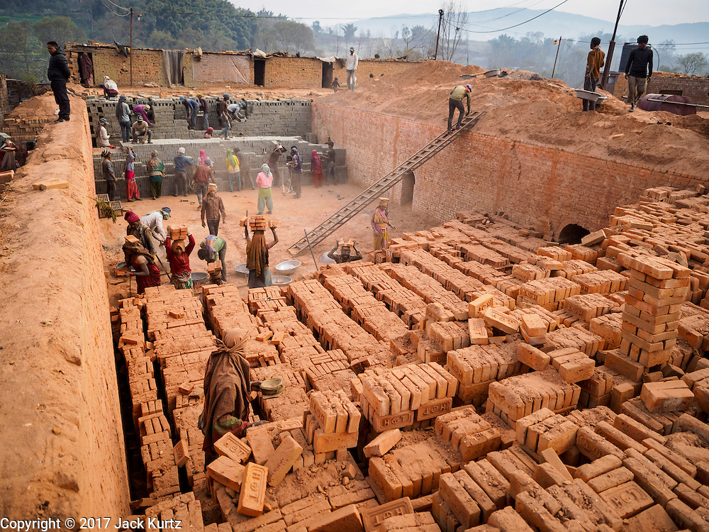 03 MARCH 2017 - BAGMATI, NEPAL: Workers carry baked bricks to waiting trucks while other workers stack wet bricks in the kiln for baking at a brick factory in Bagmati, near Bhaktapur. There are almost 50 brick factories in the valley near Bagmati. The brick makers are very busy making bricks for the reconstruction of Kathmandu, Bhaktapur and other cities in the Kathmandu valley that were badly damaged by the 2015 Nepal Earthquake. The brick factories have been in the Bagmati area for centuries because the local clay is a popular raw material for the bricks. Most of the workers in the brick factories are migrant workers from southern Nepal.       PHOTO BY JACK KURTZ