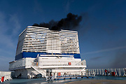 Diesel smoke pours from the funnels of Brittany Ferries roll-on / roll-off car ferry as the engines start up prior to departure on 26th September 2021 in Roscoff, Brittany, France. Brittany Ferries is the trading name of the French shipping company, BAI Bretagne Angleterre Irlande S.A. founded in 1973 by Alexis Gourvennec, that operates a fleet of ferries and cruise ferries between France and the United Kingdom.