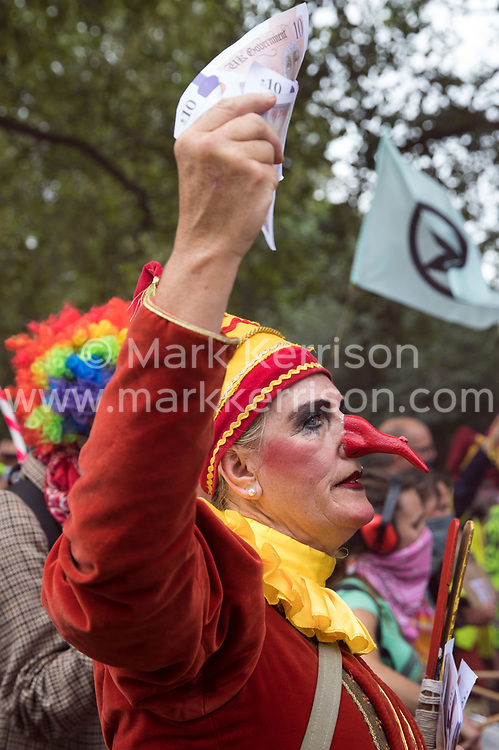 London, UK. 3rd September, 2020. A jester holding banknotes joins fellow climate activists from Extinction Rebellion at a 'Carnival of Corruption' protest against the government's facilitation and funding of the fossil fuel industry. Extinction Rebellion activists are attending a series of September Rebellion protests around the UK to call on politicians to back the Climate and Ecological Emergency Bill (CEE Bill) which requires, among other measures, a serious plan to deal with the UK's share of emissions and to halt critical rises in global temperatures and for ordinary people to be involved in future environmental planning by means of a Citizens' Assembly.