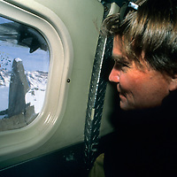 ANTARCTICA, Alex Lowe looks out Twin Otter window at Rakekniven spire, Queen Maud Land
