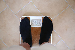 Woman standing on a set of bathroom scales,