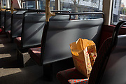 A brown paper bag from Monopoly is still on a seat of a London bus after its user has left, on 15th April 2019, in London, England.