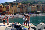 ITALY, Liguria, Camogli: vista della spiaggia.....Italy, Liguria, Camogli: reading and relaxing on the blocks.