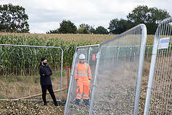 Offchurch, UK. 24th August, 2020. A HS2 worker monitors an anti-HS2 activist during tree felling works alongside the Fosse Way in connection with the HS2 high-speed rail link. The controversial HS2 infrastructure project is currently expected to cost £106bn and will destroy or significantly impact many irreplaceable natural habitats, including 108 ancient woodlands.