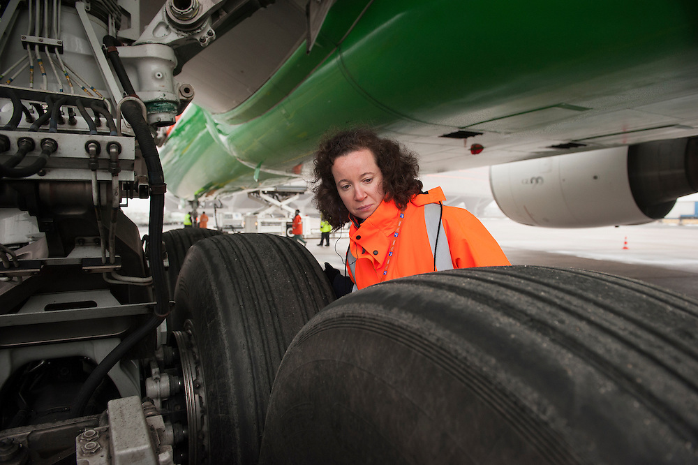 Inspection of an airplane. At Roissy, Nesrine, 34, works as a technical inspector  for the DGCA (Directorate General of Civil Aviation) - she is the only female technical controller at the airport of Roissy-en-France. She can stop a Boeing taking off and make the 300 passengers leave the airplane. Nesrine Chkioua is the only woman controller at Roissy Airport and one of three women doing this job in France.<br /> <br /> <br /> À Roissy, Nesrine, 34 ans, exerce le métier de contrôleur technique (CTE) pour la DGAC (Direction générale de l'aviation civile) - elle est la seule femme contrôleur technique à l'aéroport de Roissy-en-France.  Elle peut immobiliser un Boeing, retarder le décollage et même faire débarquer les 300 passagers d'un long-courrier. Nesrine Chkioua est la seule contrôleur femme à Roissy aéroport et est une des trois femmes à exercer ce métier en France.