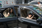 Middle class family getting into car, Beijing, China