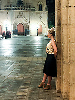 Natasha leans on an stone pillar in Castellon de la Plana, in the central square on a summer night, with the Church in the background.