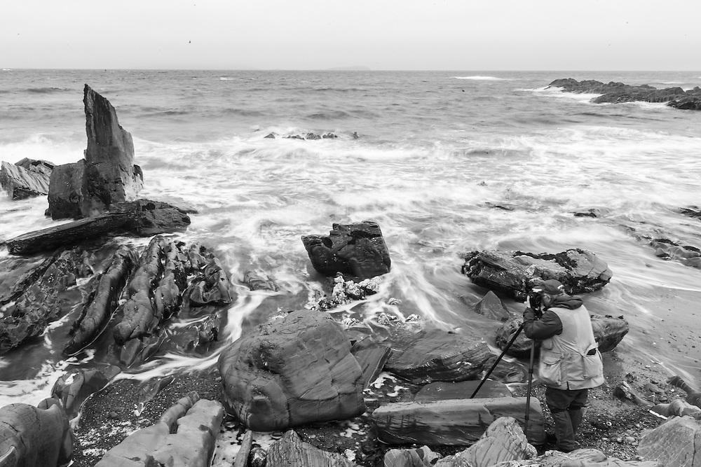 Photographer photographing waves crashing on shore and rocks of Atlantic coast, Barnabaun, County Mayo, Ireland